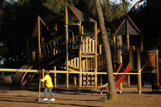 FILE - In this May 4, 2020 file photo, a child looks at a sealed-off playground at Rome's Villa Pamphili park as the park reopened after several weeks of closure, part of nationwide limited easing of some coronavirus lockdown restrictions, in Rome. A national survey of the psychological impact of coronavirus lockdowns on Italian children presented in Rome on Tuesday, June 16, 2020, has quantified what many parents noticed offhand during weeks cooped up at home: Their kids were more irritable, had trouble sleeping and for some of the youngest, wept inconsolably and regressed developmentally.   (AP Photo/Alessandra Tarantino)