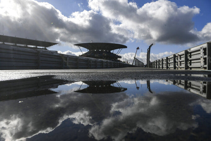 Clouds are reflected in a puddle prior to the start of the third practice session for the Eifel Formula One Grand Prix at the Nuerburgring racetrack in Nuerburg, Germany, Saturday, Oct. 10, 2020. The Germany F1 Grand Prix will be held on Sunday. (Ina Fassbender, Pool via AP)