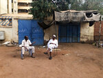Two Sudanese men sit on the street outside their house in Khartoum, Sudan, Saturday, June 15, 2019. The top U.S. diplomat to Africa says there needs to be an
