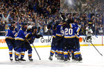 FILE - In this May 7, 2019, file photo, St. Louis Blues celebrate after defeating the Dallas Stars in double overtime in Game 7 of an NHL second-round hockey playoff series in St. Louis. The Blues won 29 of their final 43 games to go from last place in the NHL to the Western Conference final. They adopted Laura Branigan's song