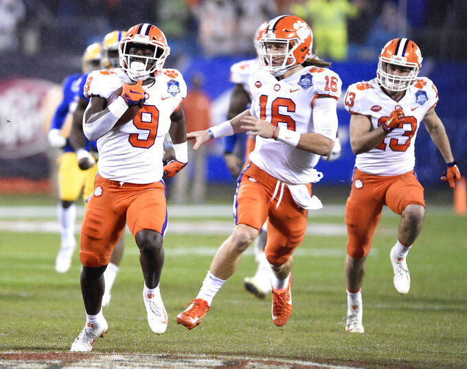 FILE - In this Saturday, Dec. 1, 2018, file photo, Clemson's Travis Etienne (9) followed by quarterback Trevor Lawrence (16) runs for a touchdown against Pittsburgh in the first half of the Atlantic Coast Conference championship NCAA college football game in Charlotte, N.C. Clemson's high-octane offense is led by the pair of young, talented offensive players. (AP Photo/Mike McCarn, File)