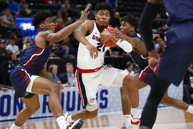 Gonzaga forward Rui Hachimura (21) drives to the basket against Fairleigh Dickinson forward Mike Holloway Jr., left, and Fairleigh Dickinson forward Elyjah Williams, right, during the first half of a first-round game in the NCAA men's college basketball tournament Thursday, March 21, 2019, in Salt Lake City. (AP Photo/Jeff Swinger)