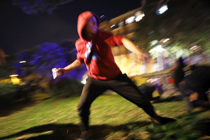A protestor hurls a rock at police during clashes in Barcelona, Spain, Wednesday, Oct. 16, 2019. Spain's government said Wednesday it would do whatever it takes to stamp out violence in Catalonia, where clashes between regional independence supporters and police have injured more than 200 people in two days. (AP Photo/Emilio Morenatti)
