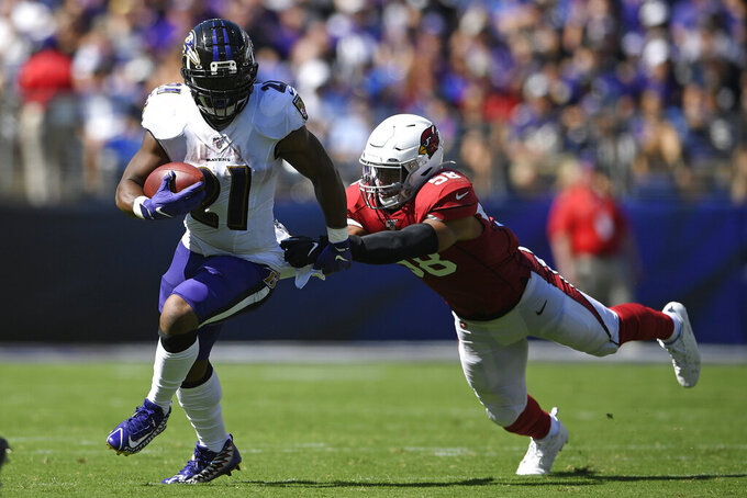Baltimore Ravens running back Mark Ingram, left, rushes past Arizona Cardinals middle linebacker Jordan Hicks in the first half of an NFL football game, Sunday, Sept. 15, 2019, in Baltimore. (AP Photo/Nick Wass)
