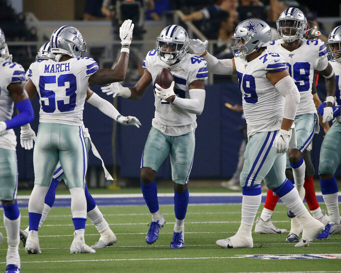 Dallas Cowboys' Justin March-Lillard (53) and others congratulate Tyvis Powell (45) after Powell intercepted a pass in the first half of a preseason NFL football game against the Tampa Bay Buccaneers in Arlington, Texas, Thursday, Aug. 29, 2019. (AP Photo/Ron Jenkins)