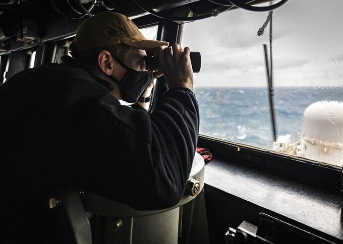 """In this photo provided by U.S. Navy, Ensign Grayson Sigler, from Corpus Christi, TX., scans the horizon while standing watch in the pilot house as guided-missile destroyer USS John S. McCain conducts routine underway operations in support of stability and security for a free and open Indo-Pacific, at the Taiwan Strait, Wednesday, Dec. 30, 2020. China accused the U.S. of staging a show of force by sailing two Navy warships through the Taiwan Strait on Thursday morning. The Navy said the Arleigh Burke-class guided missile destroyers USS John S. McCain and USS Curtis Wilbur """"conducted a routine Taiwan Strait transit"""" in accordance with international law. (Mass Communication Specialist 2nd Class Markus Castaneda/U.S. Navy via AP)"""