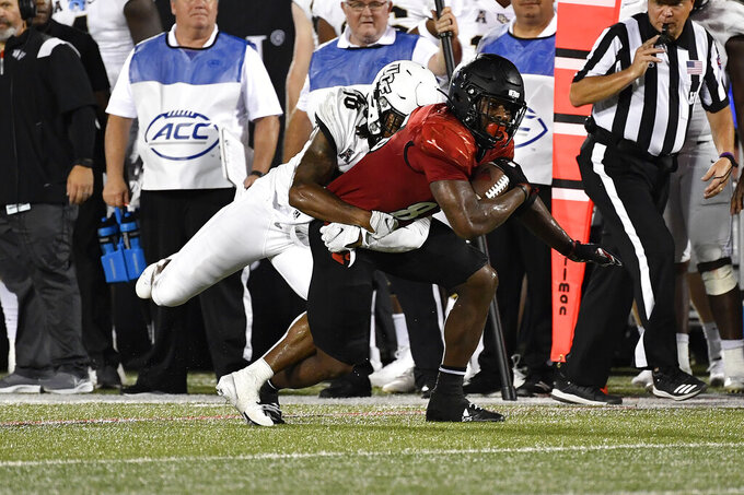 Central Florida defensive back Dyllon Lester (18) attempts to tackle Louisville tight end Marshon Ford (83) during the second half of an NCAA college football game in Louisville, Ky., Friday, Sept. 17, 2021. (AP Photo/Timothy D. Easley)
