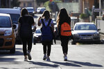 """Elena Maria Moretti, 12, center, walks with her friends to school in Rome, Thursday, June 3, 2021. The joy of rejoining the world -- and especially reuniting with friends and extended family -- has been a universal theme for the young participants who've been able to do so. """"Being with them, hugging them,"""" Moretti says. (AP Photo/Gregorio Borgia)"""
