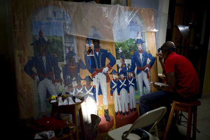 In this June 28, 2019 photo, Haitian artist Ernst Jeudy works on the restoration of a painting by Haitian artist Edouard Duval Carrie, at the Musée d'Art du Collège Saint Pierre, in Port-au-Prince, Haiti. It is one of dozens of well-known paintings that artists are still trying to rescue nearly a decade after the magnitude 7.0 quake that killed an estimated 300,000 people or more and damaged countless buildings, including the Museum of Haitian Art of St. Pierre College, one of the country's top museums. (AP Photo/Dieu Nalio Chery)