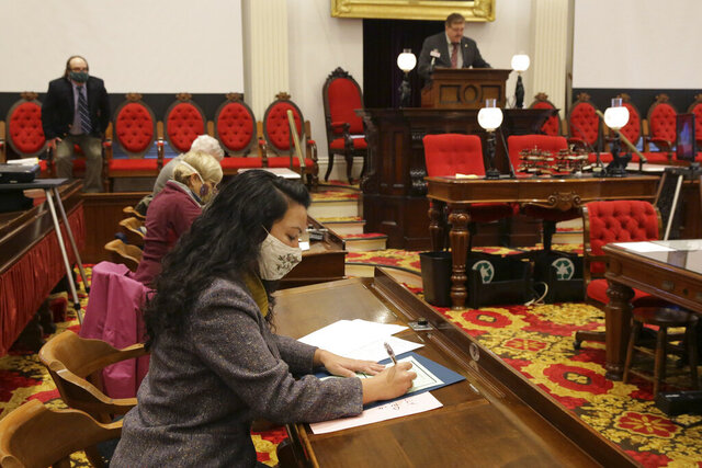 Vermont Presidential elector Kesha Ram fills out her presidential ballot at the Statehouse in Montpelier, Vt., on Monday, Dec. 14, 2020. (AP Photo/Wilson Ring)