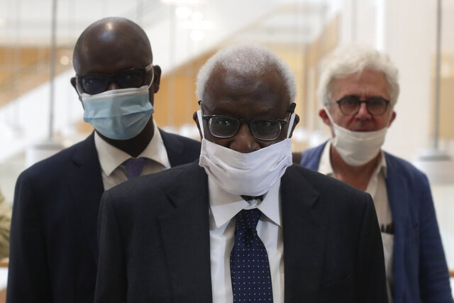 Former president of the IAAF (International Association of Athletics Federations) Lamine Diack arrives with his lawyer William Bourdon, right, at the Paris courthouse, Monday, June 8, 2020. A sweeping sports corruption trial opened Monday in Paris involving allegations of a massive doping cover-up that reached to the top of world track and field's governing body. Lamine Diack, 87, who served as president of the body for nearly 16 years, is among those accused of receiving money from Russian athletes to hide their suspected doping so they could compete at the Olympics in 2012 and other competitions. His son Papa Massata Diack is also charged in the case. (AP Photo/Thibault Camus)