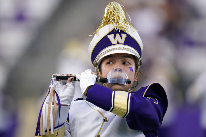 A piccolo player with the Washington Marching Band performs with a mouth shield due to the COVID-19 pandemic before an NCAA college football game against California, Saturday, Sept. 25, 2021, in Seattle. (AP Photo/Elaine Thompson)