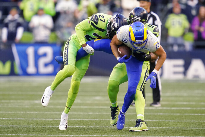 Los Angeles Rams wide receiver Cooper Kupp is wrapped up by Seattle Seahawks defensive back Marquise Blair (27) and middle linebacker Bobby Wagner (54), right, during the first half of an NFL football game, Thursday, Oct. 7, 2021, in Seattle. (AP Photo/Elaine Thompson)