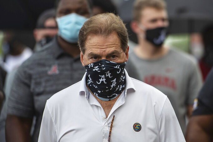 FILE - In this Aug. 31, 2020, file photo, Alabama head football coach Nick Saban leads his team as they march on campus, supporting the Black Lives Matter movement, in Tuscaloosa, Ala. The mid-week news that Alabama coach Nick Saban tested positive for COVID-19 added a challenging backdrop for the season's first Top 5 matchup. Saban figures to be communicating his marching orders and input from home while offensive coordinator Steve Sarkisian is manning the show within the football building. (AP Photo/Vasha Hunt, File)
