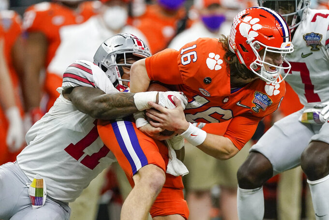 Clemson quarterback Trevor Lawrence is tackled by Ohio State defensive end Tyreke Smith during the second half of the Sugar Bowl NCAA college football game Friday, Jan. 1, 2021, in New Orleans. (AP Photo/John Bazemore)