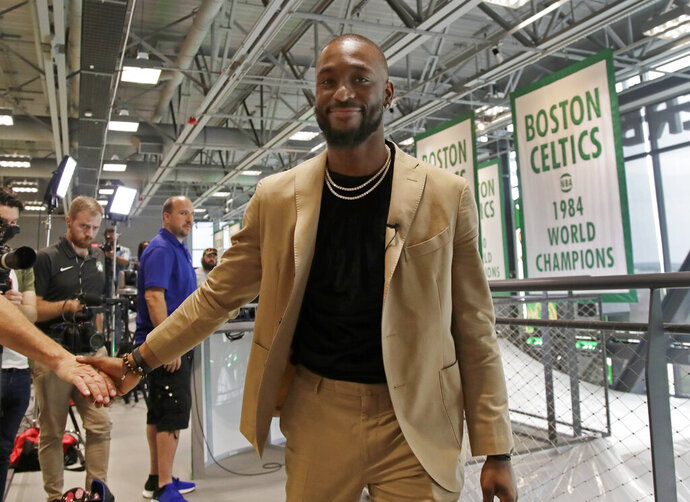 Newly acquired Boston Celtics guard Kemba Walker shakes a hand as he leaves an interview at the Celtics' basketball practice facility, Wednesday, July 17, 2019, in Boston. (AP Photo/Elise Amendola)