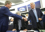 Brexit Party leader Nigel Farage, left, shakes hands with European Union chief Brexit negotiator Michel Barnier while European Commission President Jean-Claude Juncker leans forward Wednesday, Sept. 18, 2019 in Strasbourg. Members of the European Parliament discuss the current state of play of the UK's withdrawal from the EU. (AP Photo/Jean-Francois Badias)