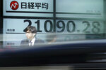 A man stands near an electronic stock board showing Japan's Nikkei 225 index at a securities firm in Tokyo Thursday, May 16, 2019. Asian shares were mixed Thursday as worries remained about trade tensions, tempered by media reports that President Donald Trump may delay a decision on auto tariffs. (AP Photo/Eugene Hoshiko)
