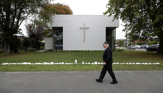 A man walks past a memorial of 50 pairs of white shoes for the victims of Friday March 15 mass mosque shootings in front of a church in Christchurch, New Zealand, Tuesday, March 19, 2019.  Four days after Friday's attack, New Zealand's deadliest shooting in modern history, relatives were anxiously waiting for word on when they can bury their loved ones. (AP Photo/Mark Baker)