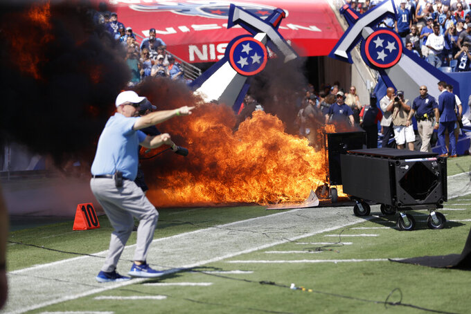 A fire from a pyrotechnics machine burns on the field before an NFL football game between the Tennessee Titans and the Indianapolis Colts Sunday, Sept. 15, 2019, in Nashville, Tenn. (AP Photo/James Kenney)