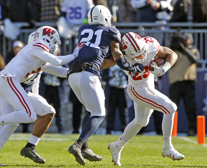 Wisconsin's Jonathan Taylor (23) is pushed out of bounds by Penn State's Amani Oruwariye (21) during the first half of an NCAA college football game in State College, Pa., Saturday, Nov. 10, 2018. (AP Photo/Chris Knight)
