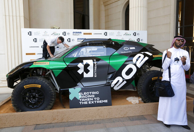 """FILE - In this Oct. 30, 2019, file photo, an electric racing series Extreme E is displayed during the Future Investment Initiative forum in Riyadh, Saudi Arabia. Andretti Autosport and Chip Ganassi Racing are the first two American teams to commit to a new electric SUV off-road racing series scheduled to begin in 2021. The Extreme E series has five events planned in what the league is calling """"some of the most remarkable, remote and severely damaged locations on the planet."""" (AP Photo/Amr Nabil, File)"""