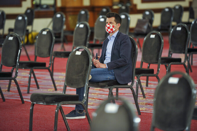 A Croatian parliament member wearing a mask with national colors attends a session at a hotel in Zagreb, Tuesday, April 7, 2020. Croatian lawmakers have met at a conference hall in a Zagreb hotel after the parliament building was damaged in a recent earthquake. The members of parliament on Tuesday were sitting individually on chairs, away from each other as part of measures designed to curb the spread of the new coronavirus. (AP Photo)
