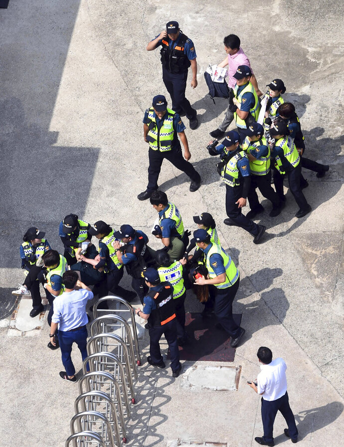 CORRECTS DATE - South Korean police officers detain protesters in front of the Japanese consulate in Busan, South Korea, Monday, July 22, 2019. South Korean police say they've detained six people for allegedly illegally entering a Japanese diplomatic facility in South Korea. (Huh Kyung-min/Newsis via AP)
