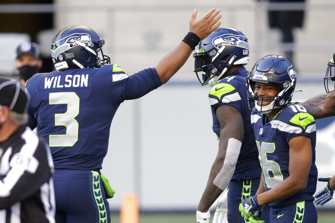 Seattle Seahawks quarterback Russell Wilson (3) celebrates with wide receiver DK Metcalf, center, after Wilson passed to Metcalf for a touchdown against the San Francisco 49ers during the first half of an NFL football game, Sunday, Nov. 1, 2020, in Seattle. (AP Photo/Scott Eklund)