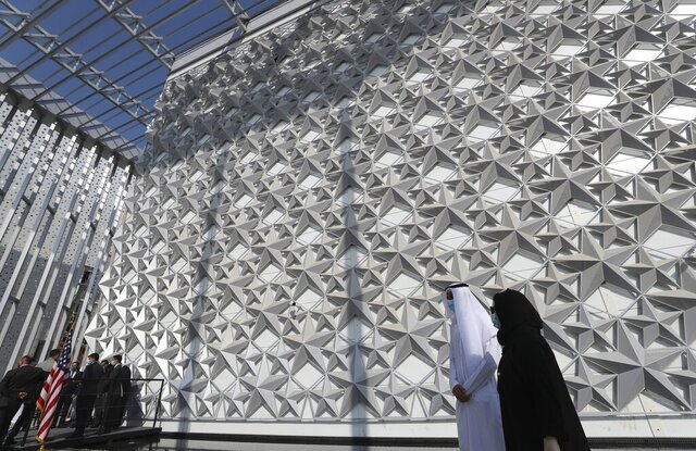 FILE - In this Nov. 18, 2020 file photo, people walk past the U.S.A Pavilion at the site of Dubai Expo 2020, in Dubai, United Arab Emirates. The UAE has relaxed and removed a range of limits on foreign ownership of companies, state-run media reported Monday, Nov. 23, 2020, in the country's latest bid to boost its global status and attract foreign investors. The dramatic changes come as the UAE has spent billions of dollars preparing to host some 25 million visitors for the World Expo, which was pushed to 2021 due to the pandemic. (AP Photo/Kamran Jebreili, File)