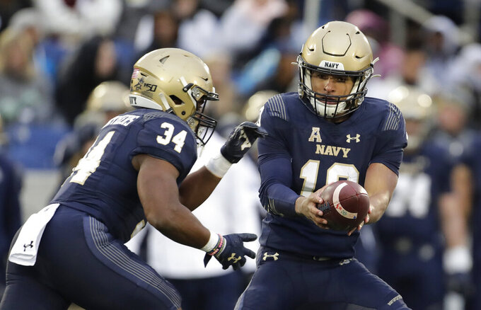 Navy quarterback Malcolm Perry, right, hands off to fullback Jamale Carothers during the first half of an NCAA college football game against SMU, Saturday, Nov. 23, 2019, in Annapolis, Md. (AP Photo/Julio Cortez)