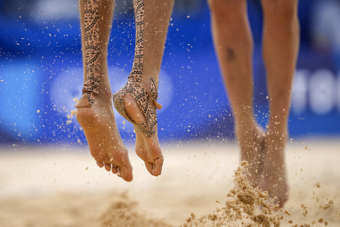 Konstantin Semenov, left, of the Russian Olympic Committee, with tape on his feet jumps during a men's beach volleyball match against Australia at the 2020 Summer Olympics, Monday, July 26, 2021, in Tokyo, Japan. (AP Photo/Petros Giannakouris)