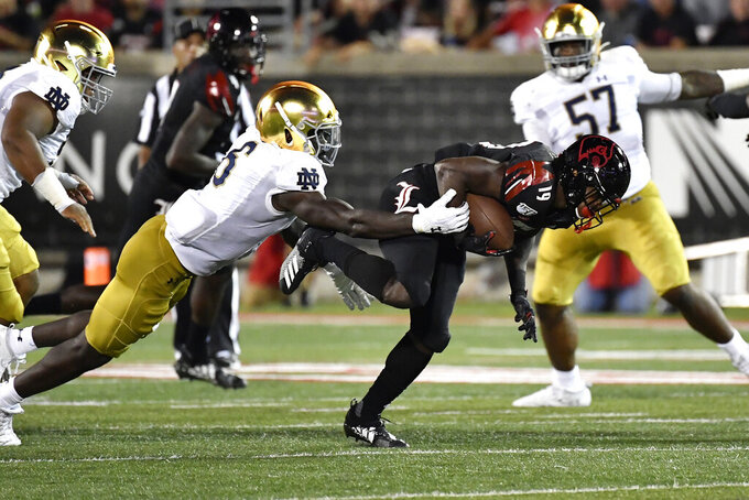 Louisville running back Hassan Hall (19) gets away from the grasp of Notre Dame linebacker Jeremiah Owusu-Koramoah (6) during the first half of an NCAA college football game in Louisville, Ky., Monday, Sept. 2, 2019. Notre Dame won 35-17. (AP Photo/Timothy D. Easley)