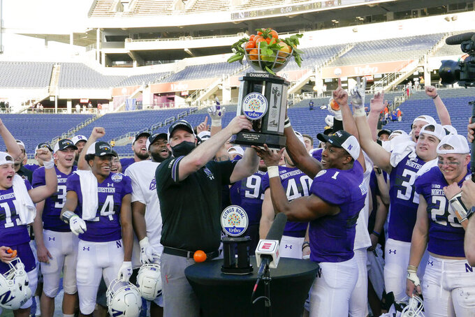 Northwestern head coach Pat Fitzgerald, front left, and Northwestern running back Jesse Brown (1) hold up the Citrus Bowl trophy and celebrate with teammates after defeating Auburn in an NCAA college football game, Friday, Jan. 1, 2021, in Orlando, Fla. (AP Photo/John Raoux)