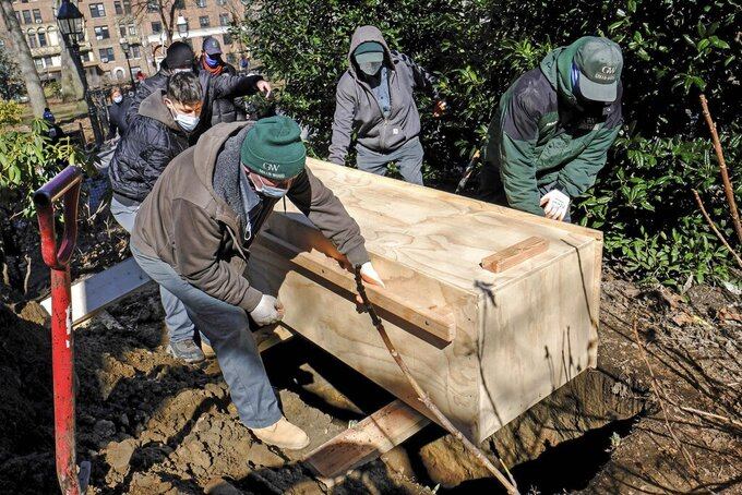 In this photo provided by the New York City Parks Department, Green-Wood Cemetery volunteers rebury the fragmentary remains of early New Yorkers found during construction in and around Washington Square Park, Tuesday, March 2, 2021, in New York. The human remains were placed in the wooden box and buried five feet below grade within a planting bed in the park, and marked with an engraved paver. (Daniel Avila/New York City Parks Department via AP)