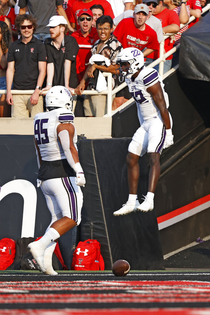 Stephen F. Austin's Willie Roberts (22) celebrates after scoring a touchdown on an interception during the first half of the team's NCAA college football game against Texas Tech, Saturday, Sept. 11, 2021, in Lubbock, Texas. (AP Photo/Brad Tollefson)