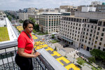 In this image provided by the Executive Office of the Mayor, District of Columbia Mayor Muriel Bowser stands on the rooftop of the Hay Adams Hotel near the White House and looks out at the words 'Black Lives Matter' that have been painted in bright yellow letters on the street by city workers and activists, Friday, June 5, 2020, in Washington. (Executive Office of the Mayor/Khalid Naji-Allah via AP)