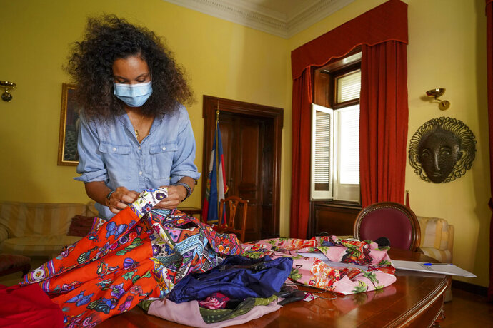 FILE - In this Aug. 13, 2020 file photo, fashion designer Stella Jean wears a face mask to curb he spread of COVID-19 as she holds fabrics during an interview with the Associated Press, in Rome. A digital runway show by five Italian fashion designers of African origin opens Milan Fashion Week on Wednesday, Feb. 24, 2020, one tangible result of a campaign launched last summer by the only Black Italian designer belonging to the Italian fashion chamber.  (AP Photo/Andrew Medichini, file)