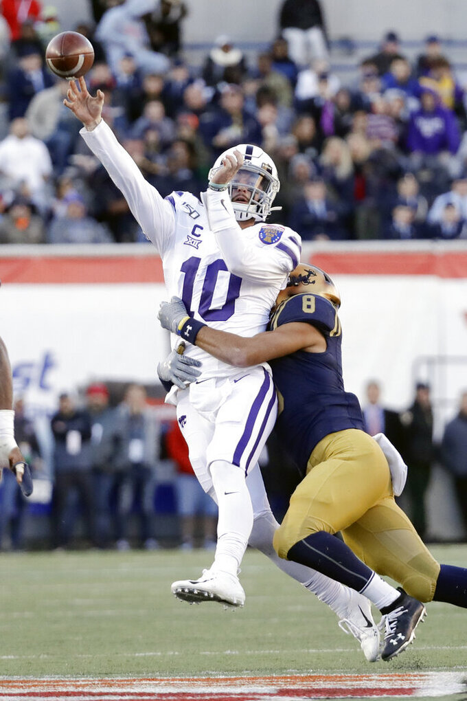 Kansas State quarterback Skylar Thompson (10) passes as he is hit by Navy safety Elan Nash (8) in the first half of the Liberty Bowl NCAA college football game Tuesday, Dec. 31, 2019, in Memphis, Tenn. (AP Photo/Mark Humphrey)