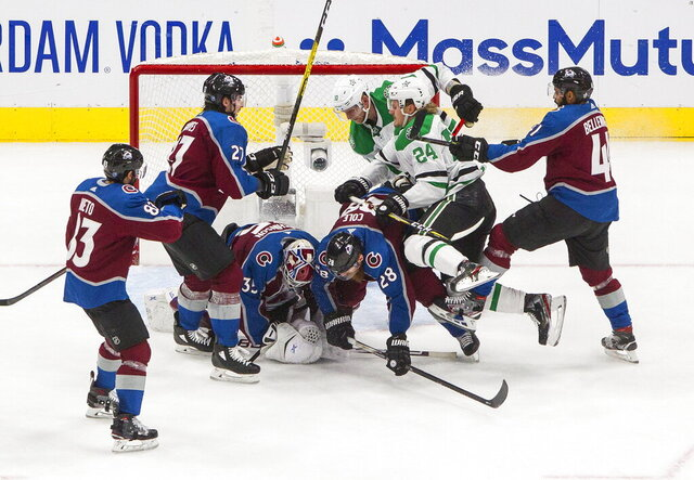 Colorado Avalanche goalie Michael Hutchinson (35) makes a save against the Dallas Stars as players scramble in front of the net during the third period of an NHL Western Conference Stanley Cup playoff game, Monday, Aug. 31, 2020, in Edmonton, Alberta. (Jason Franson/The Canadian Press via AP)
