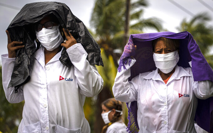 Health professionals who volunteered to travel to Kuwait to treat of coronavirus patients walk in the rain after attending their farewell ceremony in Havana, Cuba, Thursday, June 4, 2020. (AP Photo/Ramon Espinosa)