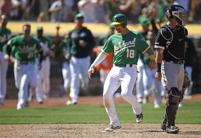 Oakland Athletics' Chad Pinder (18) scored the game winning run behind Chicago White Sox catcher James McCann in the ninth inning of a baseball game Sunday, July 14, 2019, in Oakland, Calif. Pinder scored on a throwing error by Chicago's Jose Rondon. (AP Photo/Ben Margot)
