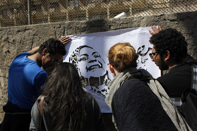 FILE - In this March 9, 2012, file photo, activists spray paint graffiti that reads in Arabic,