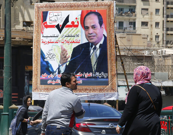People walk past a banner supporting proposed amendments to the Egyptian constitution with a poster of Egyptian President Abdel-Fattah el-Sissi in Cairo, Egypt, Tuesday, April 16, 2019. Egypt's parliament was holding its last debate Tuesday on proposed amendments to the constitution that could see President Abdel-Fattah el-Sissi remain in power until 2030. Arabic reads,