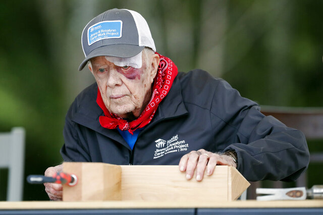 FILE- In this Oct. 7, 2019 file photo, former President Jimmy Carter builds corbels at a Habitat for Humanity project in Nashville, Tenn. Carter fell at home, requiring 14 stitches, but he did not let his injuries keep him from participating in his 36th building project with the nonprofit Christian housing organization. Carter, the longest serving president in U.S. history, recovered from several falls this year.  This was one of the top stories in Georgia in 2019. (AP Photo/Mark Humphrey)