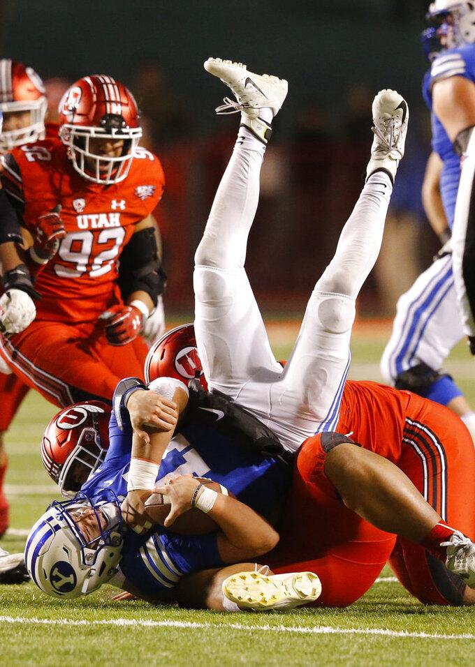 Utah Utes defensive tackle Leki Fotu, rear, sacks BYU quarterback Zach Wilson (11) in the second half during an NCAA college football game Saturday, Nov. 24, 2018, in Salt Lake City. Utah won, 35-27. (AP Photo/Rick Bowmer)