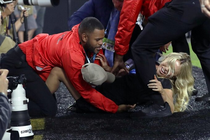 Security personnel tackle a woman who tried to run onto the field during the first half of the NFL Super Bowl 54 football game between the San Francisco 49ers and the Kansas City Chiefs Sunday, Feb. 2, 2020, in Miami Gardens, Fla. (AP Photo/John Bazemore)