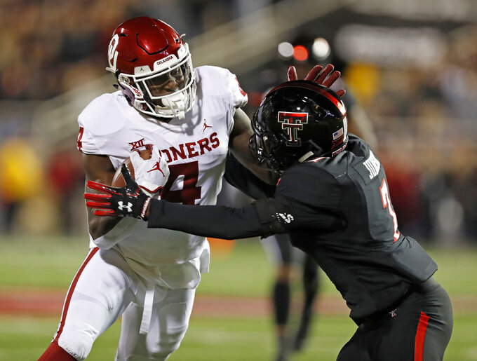 Oklahoma's Trey Sermon (4) tries to break away from Texas Tech's Jah'Shawn Johnson (7) during the first half of an NCAA college football game Saturday, Nov. 3, 2018, in Lubbock, Texas. (AP Photo/Brad Tollefson)