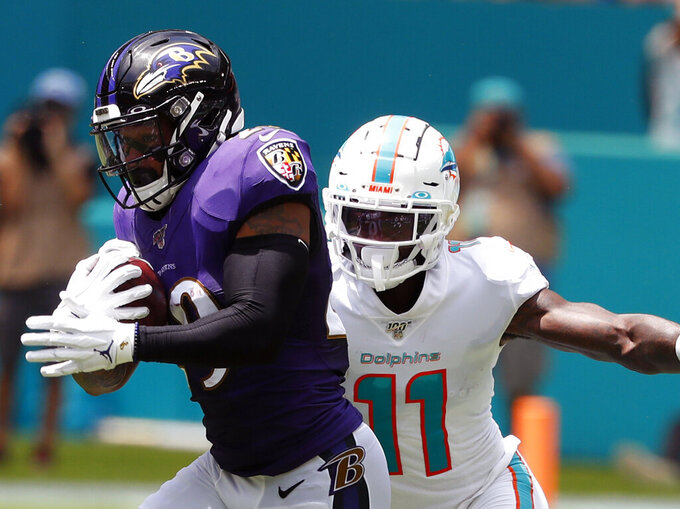 FILE - In this Sept. 8, 2019, file photo, Baltimore Ravens free safety Earl Thomas (29) intercepts a pass as Miami Dolphins wide receiver DeVante Parker (11) attempts a tackle during the first half at an NFL football game in Miami Gardens, Fla. Thomas is still unsigned as Week 1 of the NFL season begins. (AP Photo/Wilfredo Lee, File)