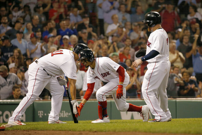 Boston Red Sox's Mookie Betts, center, is congratulated by Rafael Devers (11) after hitting a three-run home run during the second inning of the team's baseball game against the Minnesota Twins, Wednesday, Sept. 4, 2019, in Boston. (AP Photo/Mary Schwalm)